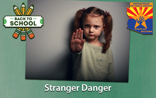 little girl hand stretch out in a stop gesture. text Stranger danger underneath the light girl.