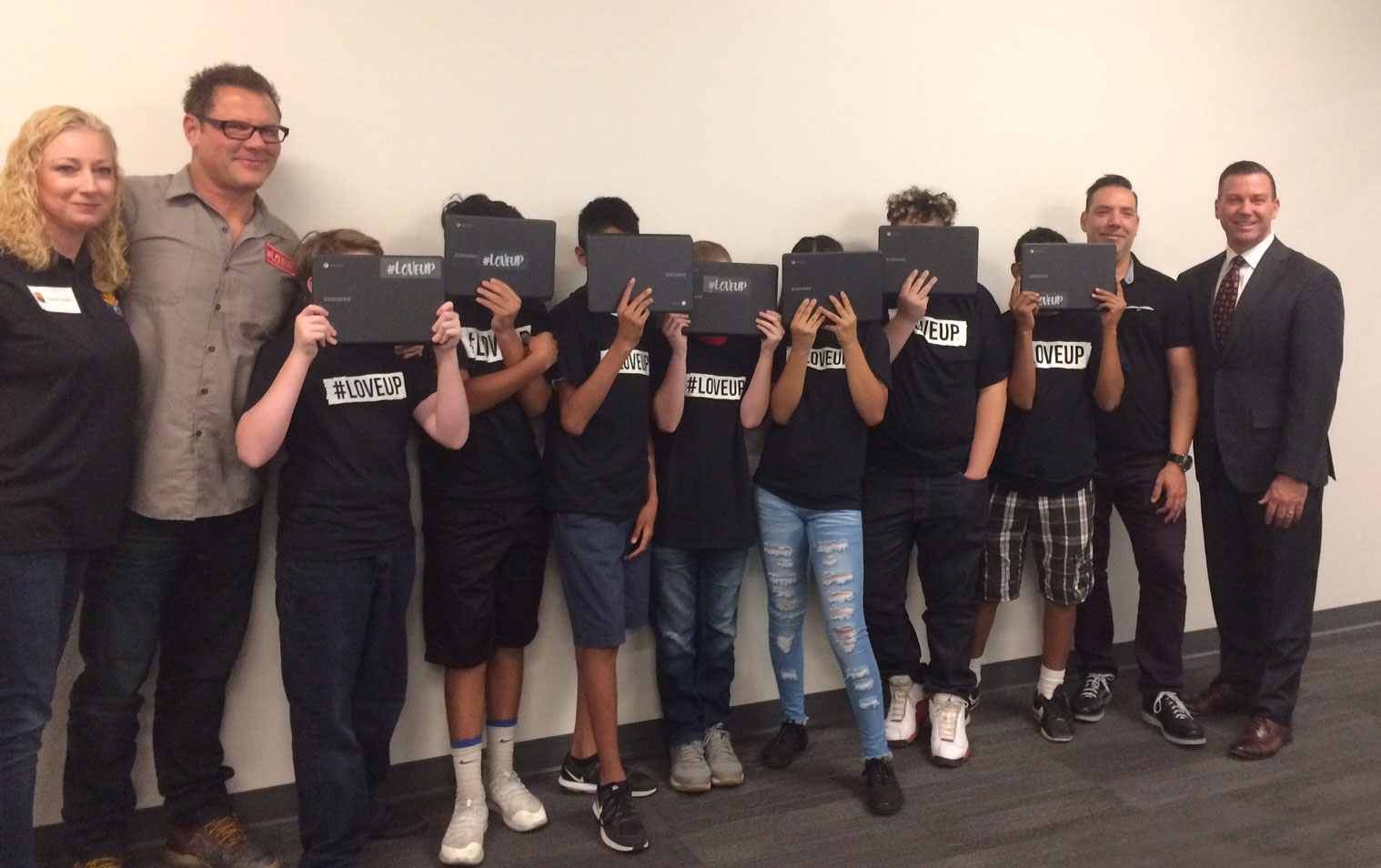 Pictured from left: DCS Deputy Director Shalom Jacobs; #LoveUp Foundation founder, Johnjay Van Es; foster youth posing with their new laptops; #LoveUp Foundation co-founder, Rich Berra; and DCS Director Greg McKay.